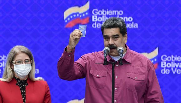 El presidente venezolano, Nicolás Maduro, acompañado de su esposa Cilia Flores hace gestos mientras brinda una conferencia de prensa en un colegio electoral en la escuela Simón Rodríguez, en Fuerte Tiuna, Caracas. (Yuri CORTEZ / AFP)