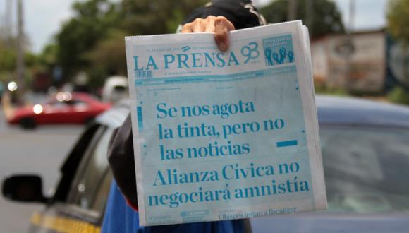 """Un vendedor de periódicos muestra la portada de """"La Prensa"""" que imprimió su portada en cian con el titular """"Se nos agota la tinta, pero no las noticias"""". (Foto: AFP)"""