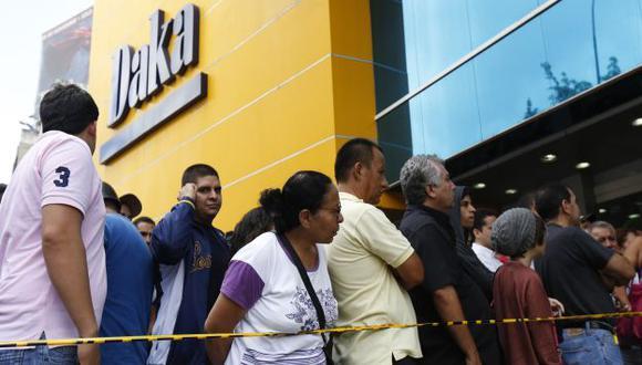 Los venezolanos hacen colas frente comercia}os ante saqueo legal dispuesto por el Gobierno. (Reuters)