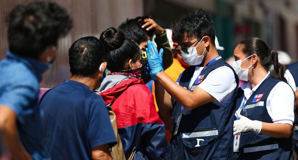 Los trabajadores de salud de Chile verifican la temperatura a las personas que se ubican en los exteriores del consulado peruano en la ciudad de Arica, el 23 de marzo de 2020. (AFP).
