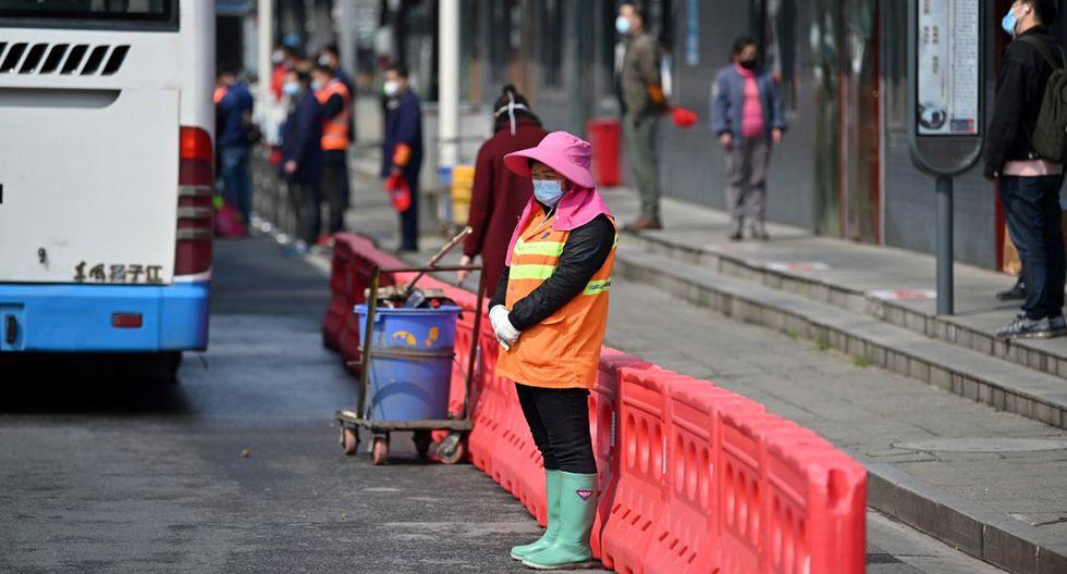 Trabajadora de la ciudad de Wuhan, cuna de la pandemia, hace una pausa para rendir homenaje a los fallecidos por el coronavirus. (Foto: AFP/Héctor Retamal)
