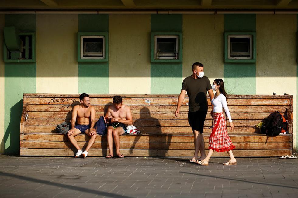 Una pareja que lleva máscaras protectoras pasa frente a un banco en Tel Aviv, Israel. (REUTERS/Corinna Kern).