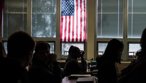 Los estudiantes de Sidney High School se sientan en clase bajo una bandera estadounidense en Ohio. En esta escuela, los profesores tienen acceso a armas de fuego para actuar en caso de tiroteos. (Foto: AFP)