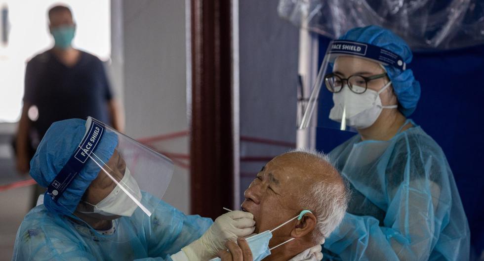 Un taxista (centro) se somete a una prueba de hisopo en un improvisado laboratorio de pruebas de coronavirus en un estacionamiento en Hong Kong. Imagen referencial del 23 de julio de 2020. (EFE/EPA/JEROME FAVRE).