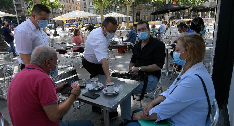 Imagen referencial. En medio de la pandemia de coronavirus, las personas con mascarillas se sientan en un bar con terraza en Las Ramblas de Barcelona. Archivo del 25 de mayo de 2020. (LLUIS GENE / AFP).