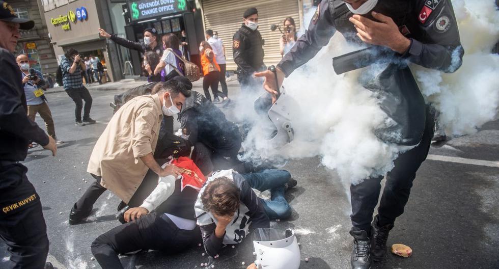 Un policía turco se encuentra en una nube de gas lacrimógeno después de que accidentalmente soltara una lata en Estambul, Turquía, el 1 de mayo de 2021. (BULENT KILIC / AFP).