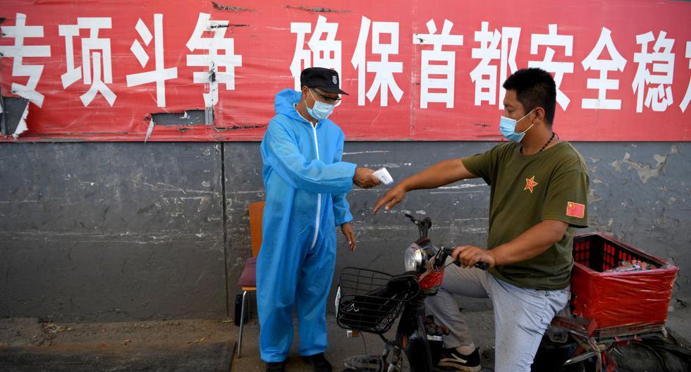 Un personal de seguridad que usa un traje de protección verifica la temperatura de un hombre en una motocicleta. (AFP / NOEL CELIS)