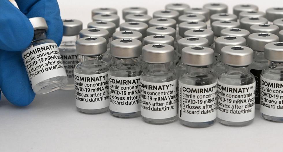 Un trabajador de la salud sostiene un frasco vacío de la vacuna Comirnaty de Pfizer/BioNTech contra el coronavirus. (Christof STACHE / AFP).