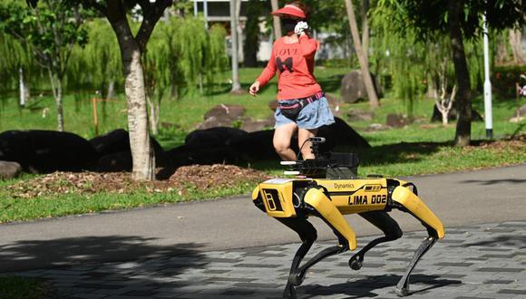 Una mujer pasa corriendo junto a un perro-robot llamado Spot en Singapur. (AFP / Roslan RAHMAN).