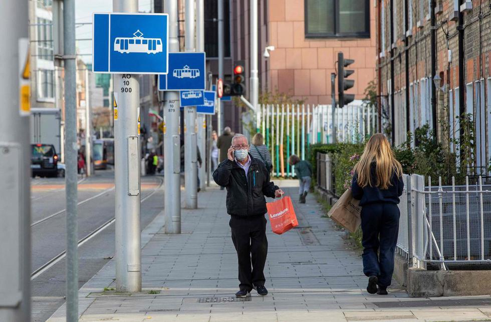 Un hombre que usa una mascarilla como precaución contra la transmisión del nuevo coronavirus camina por una calle en Dublín (Irlanda). (AFP / Paul Faith).