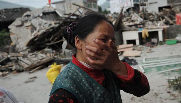 DESCONSUELO. Una mujer llora al ver destruida su vivienda y al no poder ubicar a sus familiares. (AP)