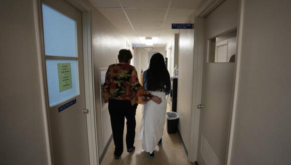 Personal de la clínica acompaña del brazo a una mujer a quien se le practicó un aborto. (Foto: AP)