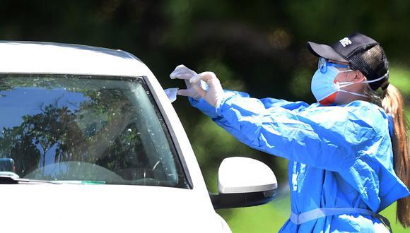 Un voluntario de atención médica en equipo de protección entrega un nuevo kit de prueba de coronavirus, COVID-19, a un conductor en un sitio de prueba móvil en Los Angeles, California. (Foto: AFP/Frederic J. BROWN)