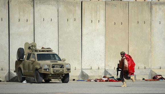 Un combatiente de la fuerza especial talibán Badri corre con una manta en el aeropuerto de Kabul (Afganistán), el 31 de agosto de 2021. (WAKIL KOHSAR / AFP).