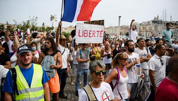"""Un manifestante sostiene un cartel que dice """"Libertad"""" mientras otros ondean banderas nacionales francesas durante una manifestación contra la vacunación obligatoria para ciertos trabajadores y el uso obligatorio del pase de salud convocado por el gobierno francés, en Marsella, sur de Francia. (CLEMENT MAHOUDEAU / AFP)"""