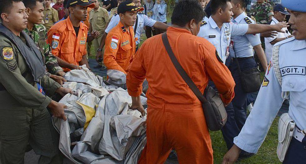 Autoridades cargan algunas partes recuperadas del avión de AirAsia. (AP)