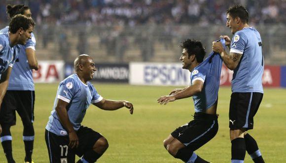 'CELESTE' EUFORIA. Arévalo Ríos y 'Cebolla' Rodríguez festejan con 'Nico' Lodeiro, autor del 2-0. (AP)