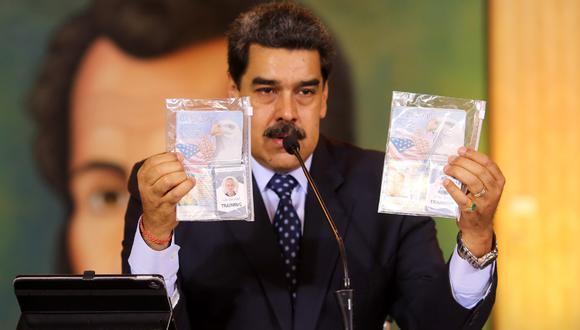 Presidente venezolano, Nicolás Maduro, que muestra los pasaportes de dos ciudadanos estadounidenses arrestados por las fuerzas de seguridad durante una reunión de video conferencia con corresponsales de medios internacionales, en el Palacio Presidencial de Miraflores en Caracas. (Foto: AFP/Marcelo García/Presidencia venezolana)