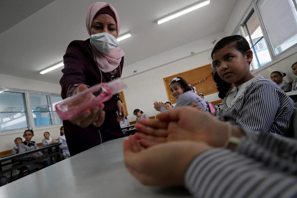 Una maestra con una mascarilla protectora por el coronavirus desinfecta las manos de un estudiante en la ciudad de Gaza. (REUTERS/Mohammed Salem).