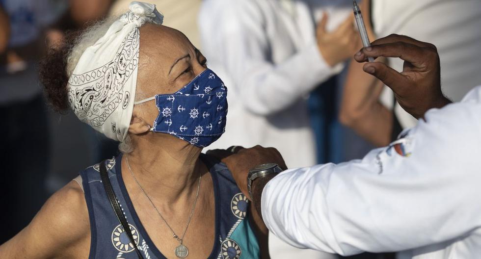 Un trabajador de la salud muestra la jeringa a una mujer después de inyectarle una dosis de la vacuna Sinovac, en Duque de Caxias, Brasil, el miércoles 24 de marzo de 2021.  (AP/Silvia Izquierdo).