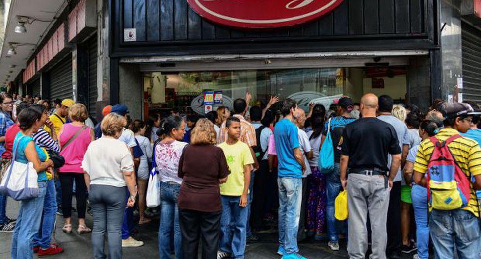 La gente espera afuera de un supermercado durante un apagón en Caracas el 30 de agosto de 2018. (Foto referencial: AFP)