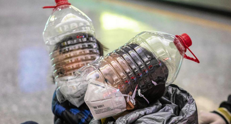 Niños con máscaras, guantes y botellas de agua modificadas se sientan en un carro en la terminal de llegadas del aeropuerto de Guangzhou en China. (EFE).