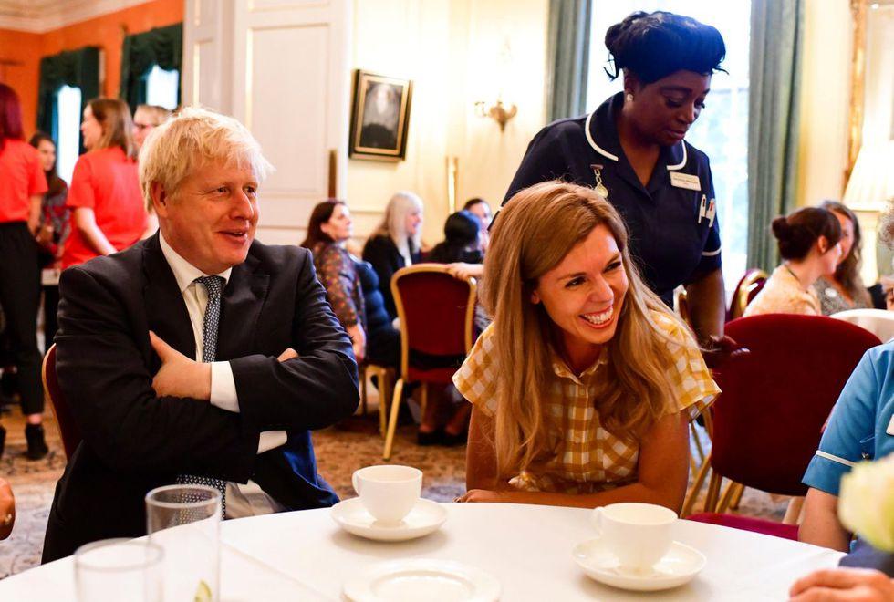 El primer ministro de Gran Bretaña, Boris Johnson, se sienta junto a su pareja Carrie Symonds. (Foto: Reuters).