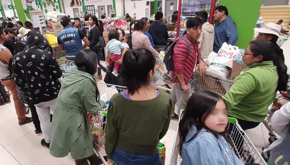 Personas forman largas colas para comprar productos de primera necesidad.