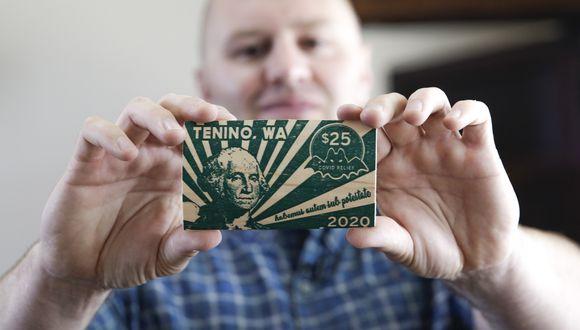Como el museo de la ciudad tiene una impresora que data de 1890, la utilizaron para hacer 10.000 dólares en rectángulos de madera, cada uno con un valor nominal de 25 dólares.. (Photo by Jason Redmond / AFP)