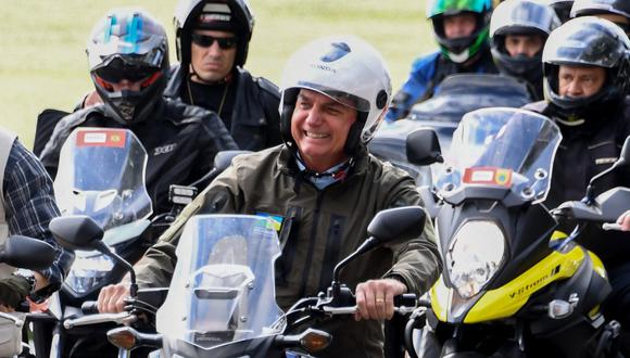 Al final del recorrido, Bolsonaro, férreo crítico del confinamiento social para enfrentar la pandemia, se tomó fotografías, estrechó manos con decenas de seguidores que, al igual que él, no llevaban mascarilla. (Foto: EVARISTO SA / AFP)
