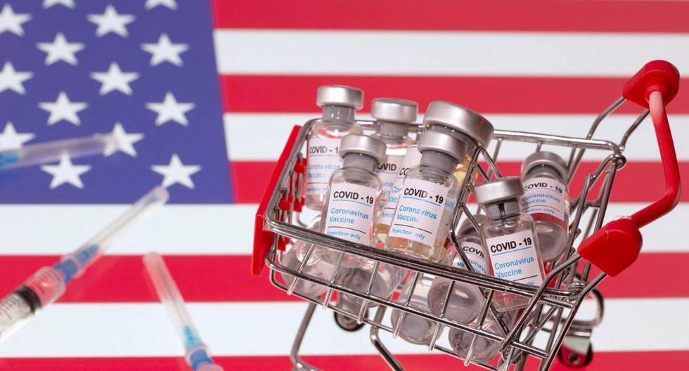 """Una pequeña canasta de compras llena de viales con la etiqueta """"COVID-19 - Vacuna contra el coronavirus"""" y jeringas médicas se colocan en una bandera de Estados Unidos. Fotografía tomada el 29 de noviembre de 2020. (REUTERS/Dado Ruvic)."""