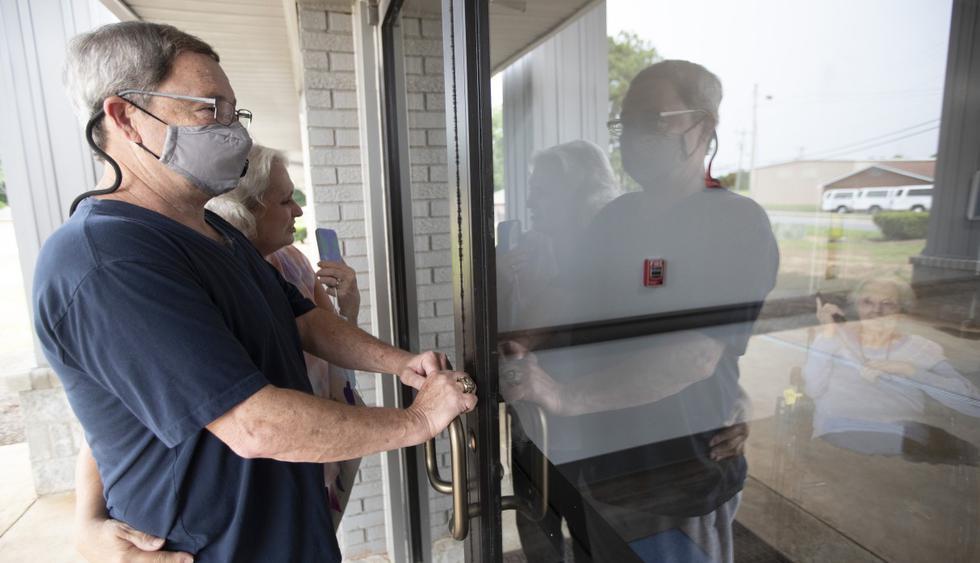 """Los residentes de """"Southern Pines"""" aún tienen que conformarse con ver a sus seres queridos a través de ventanas y paneles, lo que les priva del contacto. (AP/John Bazemore)."""