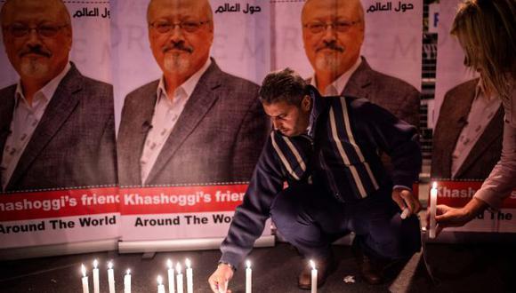 Un hombre enciende velas en carteles que representan al periodista saudita Jamal Khashoggi durante una reunión frente al consulado de Arabia Saudita en Estambul. (Foto: AFP)