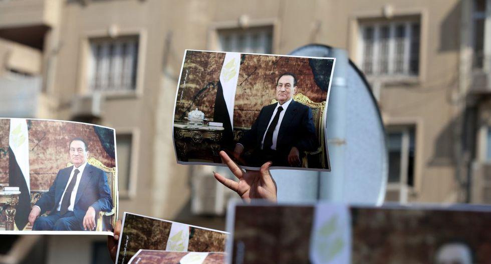 Los nostálgicos del régimen que no pudieron presenciar el funeral lloraron ante las cámaras de los periodistas por la muerte del líder, envueltos en camisetas, sosteniendo pancartas y llevando chapas con imágenes del difunto dictador. (EFE).