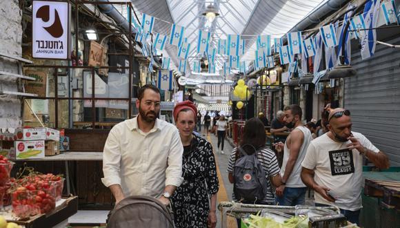 La gente compra en un mercado en Jerusalén, el 18 de abril de 2021, después de que las autoridades israelíes anunciaran que las mascarillas para la prevención del COVID-19 ya no eran necesarias al aire libre. (Menahem Kahana / AFP)