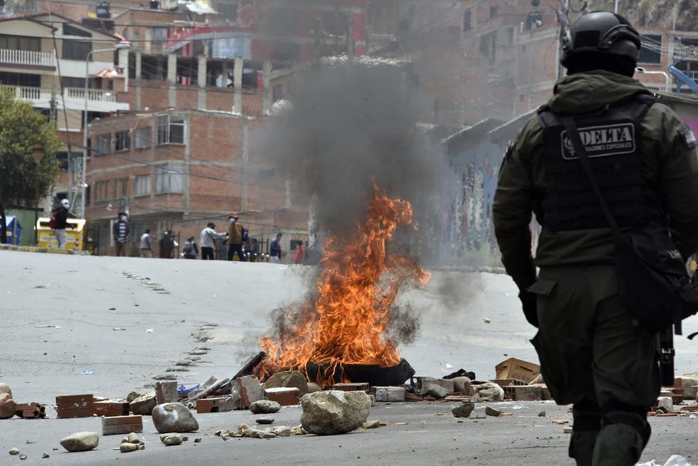 Un policía antidisturbios camina cerca de una hoguera durante los enfrentamientos con un grupo de productores de hoja de coca que intentaban apoderarse del Mercado de Coca en La Paz, Bolivia. (Foto: AIZAR RALDES/AFP)