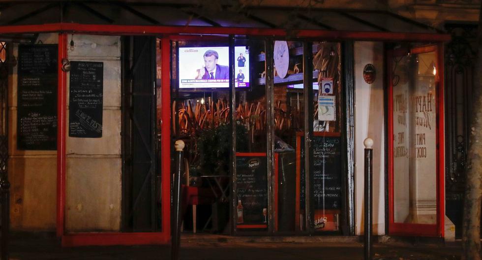El presidente de Francia, Emmanuel Macron, es visto en una pantalla de televisión en un bar cerrado en París, el 14 de octubre de 2020. (REUTERS/Gonzalo Fuentes).