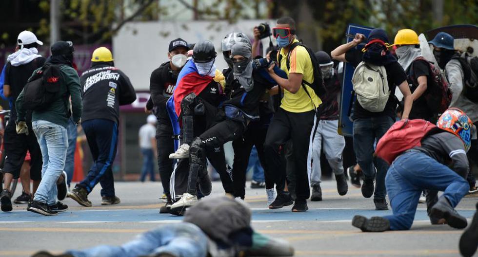 Un hombre ayudado por compañeros manifestantes luego de ser alcanzado por una bala durante enfrentamientos con la policía en el marco de una nueva protesta contra el gobierno del presidente colombiano Iván Duque, en Cali, Colombia, el 28 de mayo de 2021. (Luis ROBAYO / AFP).