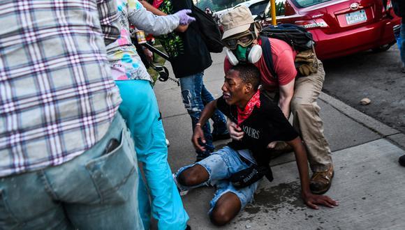 Un hombre recibe asistencia después de ser alcanzado por gases lacrimógenos cerca del quinto recinto policial durante una manifestación para pedir justicia para George Floyd, un hombre afroamericano que murió mientras estaba bajo custodia de la policía de Minneapolis. (Foto: AFP/CHANDAN KHANNA)