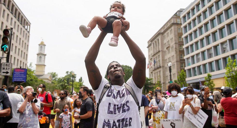 Un manifestante sostiene a un niño durante una protesta por la muerte de George Floyd cerca de la Casa Blanca, en Washington. (REUTERS/Eric Thayer).