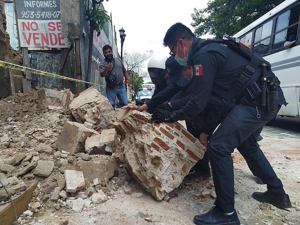 Policías y elementos de Protección Civil levantan parte de una barda derrumbada en la ciudad de Oaxaca. (Foto: EFE/Daniel Ricardez)