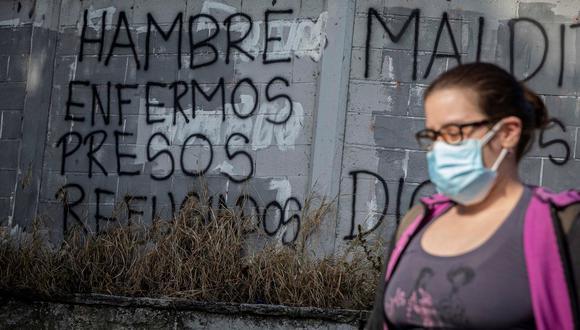 """Una mujer camina frente a una pared con un graffiti pintado que dice """"Hambre, enfermos, presos, refugiados"""" el 8 de febrero de 2021, en Caracas (Venezuela). EFE/ Rayner Peña R"""