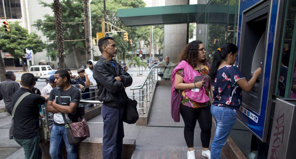 """Una mujer retira nuevos billetes venezolanos de """"bolívares soberanos"""" desde un cajero automático en Caracas, Venezuela. (AP)"""