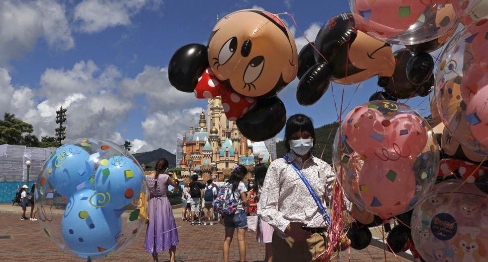 Un empleado, que usa una máscara facial para prevenir la propagación del nuevo coronavirus, vende globos en Hong Kong Disneyland. Imagel del jueves 18 de junio de 2020.  (AP/Kin Cheung).