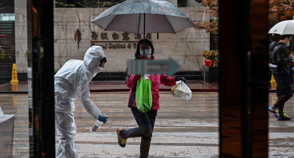 Un empleado del hotel con un traje protector rocía desinfectante a un huésped que llega, como medida preventiva contra el coronavirus en Wuhan, la provincia central de Hubei de China. (Foto: AFP/Héctor Retamal)