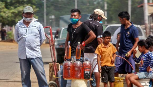 La gente ofrece gasolina a la venta en las calles de Maracaibo, estado de Zulia, Venezuela, en medio de la pandemia de coronavirus COVID-19. (AFP/Luis BRAVO).