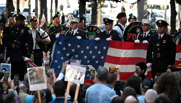 La policía y los bomberos de Nueva York sostienen una bandera de los EE. UU. durante una ceremonia que conmemora el 20 aniversario de los ataques del 11 de septiembre en el World Trade Center, en Nueva York.  (Foto: Jim WATSON / AFP)