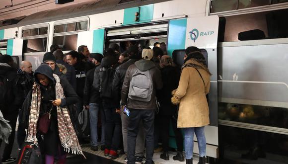 Los viajeros abordan un tren en la estación de tren suburbano Nation en París, durante una huelga de empleados del operador de transportes públicos de París RATP.