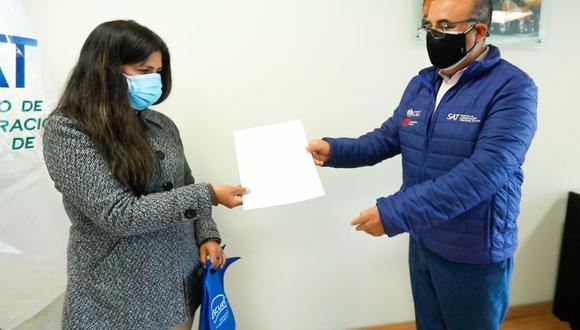 El jefe del SAT de Lima, Miguel Roa, entregó el dinero a la mujer que había extraviado 1300 soles en la sede principal de la entidad. (Foto: Servicio de Administración de Lima)