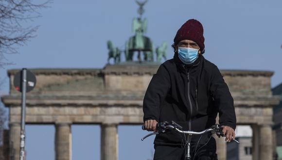 Un hombre con una máscara facial se desplaza frente a la Puerta de Brandenburgo en Berlín, en medio de la pandemia del COVID-19. (Foto: AFP/John MACDOUGALL)